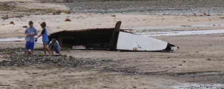 Children play near the remains of a catamaran.