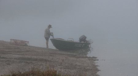 Keen fisherman prepares to collect crabpots in early morning fog.