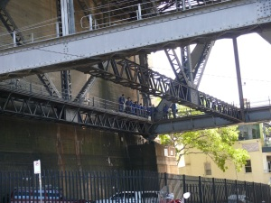 A Sydney Bridge Climb tour group almost completing their tour. A little to the left in this photo is a hole in the wall tunnel. All tours commence and end inside the tunnel.
