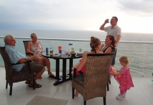 Happy hour on the balcony overlooking the ocean on the 10th floor beachside hotel. l toR. Doug, Linda, Errol, Nicole with Alecia with back to camera holding baby Hannah and toddler Amelia.