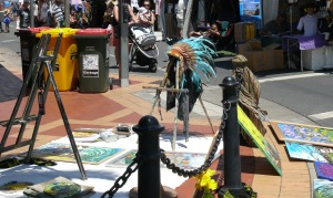 An artist places all his paintings on the street. Not sure why he has an indian headdress on display.