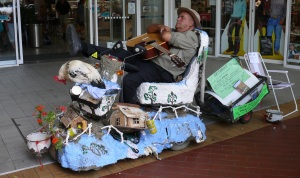 This is the Chookman. He roams around the streets on his battery wheelchair, strumming the guitar towing a night pot for people to throw coins into. Yes that is a real, live chook at the front and yest it also was asleep.