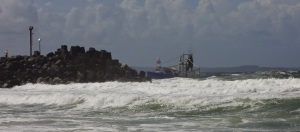 Fishing boat crossing the bar at the entrance to Forster rockwalls.