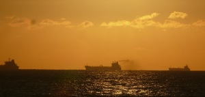 Early morning sunrise showing a ship at anchor bathed in a golden glow.