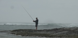 Barefoot fisherman on the rocks in heavy rain at Woody Head.