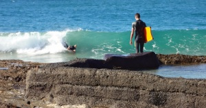 These young Boogey Boarders were catching waves and pulling out just before slamming into the rocks. The rider standing did not have a leg strap and lost his board twice. He had to climb on the rocks to retrive it.