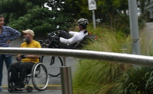 A recumbent cyclists has just riddeen uo a short steep hill near the maritime museum and a wheelchair bound man has just pushed up the opposite slope.