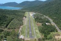 Whitsunday Coast Airport with Flametree Tourist Village about midway on the right beside the Shute Harbour Road and Shute Harbour in the distance.