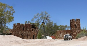 Castle at Lightning Ridge hand built from local rock among the moonscape of  tailings from exploration mining shafts.