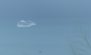 The cruise ship is difficult to see as low cloud and a rain front is heading towards the bay.