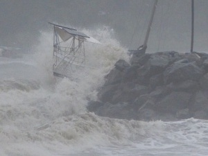 Waves continue to pound the yacht against the rocks.