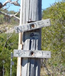 Hmmm! Old worn sign at Grey's Beach.