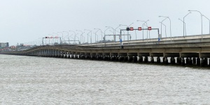 The second bridge to Redcliffe with the familiar hump in the middle to allow larger boats to pass underneath in the deepest section of the bay. Enlarge the photo and you can see the latest bridge behind. It is far higher above the water . The bridge traffic is controlled by traffic lights and speed advisory signs and strong lighting as the area is subject to fog.