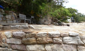 Sandstone retaining wall forming a sandstone deck area shaded by gum trees and cooled by sea breezes. Sigh!