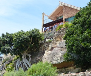 House built over sandstone cliffs at Gunyah Beach. Note the root system of a ficus growing out of the sandstone.