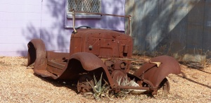 Old car in the front yard of an old mud brick dwelling.