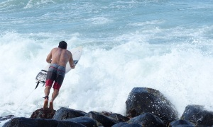Surfers had to brave a few obstacles in order to launch themselves into the surf then try to paddle against the waves without being washed back onto the rocks.