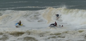 Surfers and jet skis on whipped surf.