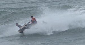 Surfer being launched by a jet ski.