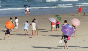 A few of the colourful umbrella toting Asian ladies on the beach at...The Spit.