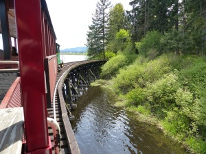 The small train crosses a trestle bridge.