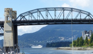 Burrage Street Bridge seen from GRANVILLE iSLAND with cruise ship and mountains in the background.