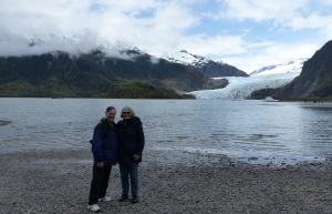 a couple rugged up against the cold and biting wind pose before the Mendenhall Glacier.