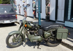 This is the Royal Enfield C5 Military motorcycle probably circa 2010 or perhaps earlier. Located in a Skagway street. Oh, and notice the small totems in the background.