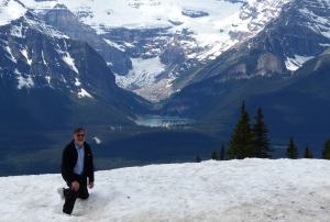 On a patch of snow with view of Lake Louise.