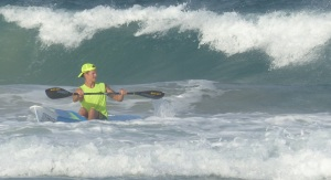Surf Ski paddler catching a final wave into the beach.