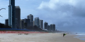 in this and the following 3 photos depicts a kite surfer walking along the beach and his preparation to take off.