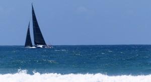 Yacht with black sails cruises along a bumpy sea.