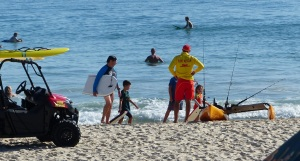 Frank, members of the public and lifeguards are fascinated by this Hobie Canoe with extra ama and trampoline.