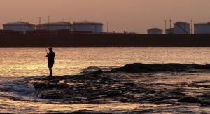 Fisherman Silhouted by setting sun beyond the Port Botany Fuel storage.